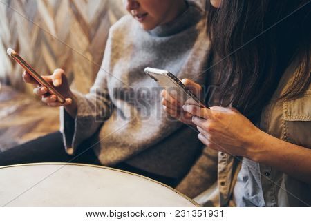 Two Woman With Smartphones In Hands Are Discussing New Trends And Work Together. Close-up Of Mobile