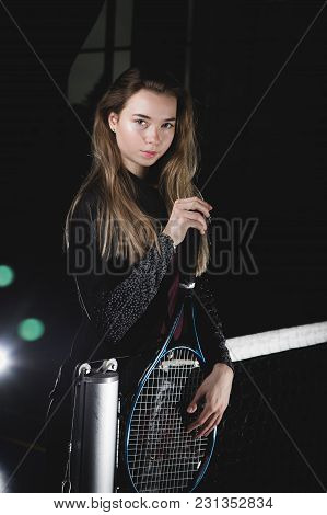 A Portrait Of A Female Tennis Player With A Racket Posing In Studio