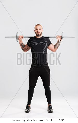Full lenght picture of strong healthy young sportsman. Looking camera make sports exercises with barbell.