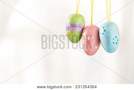 Three Decorated Easter Eggs Hang From Yellow Strings. They Dangle In Front Of A White Background And