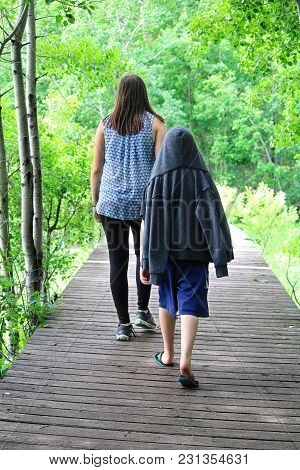 A Young Boy Following A Girl On A Boardwalk On A Tail.