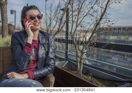 Beautiful Smiling Young Woman Sitting Outdoors And Talking On Mobile Phone