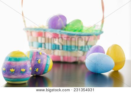 An Easter Basket Is Filled With Easter Eggs. Ceramic A Plastic Decorated Eggs Lay In Front Of The Ba