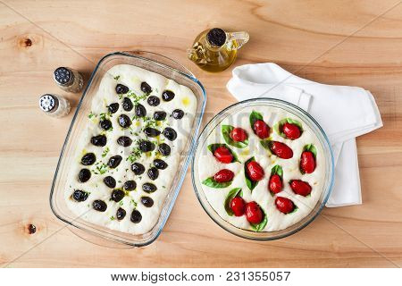 Preparation Of Focaccia With Olives And Tomatoes. Raw Dough In Glass Sheet Left To Leavening On A Wo