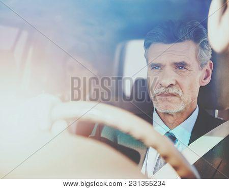 Mature Confident Successful  Businessman  In Suit Driving His Luxurious Car.