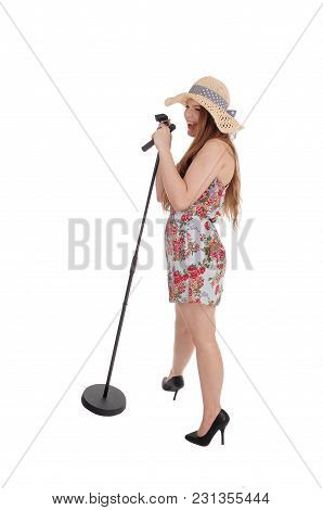 A Beautiful Young Woman Standing In Front Of A Microphone In A Dress And Singing, Wearing A Hat, Iso