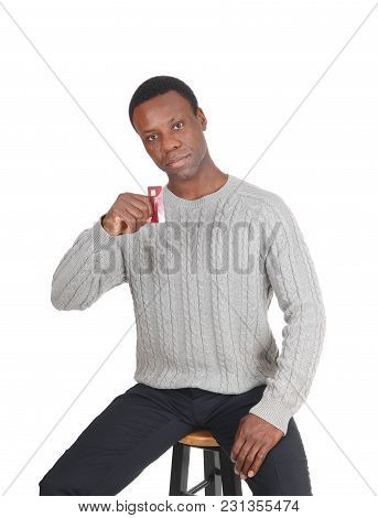 A Handsome Young African American Man Sitting In A Gray Sweater And Holding Up His New Credit Card,