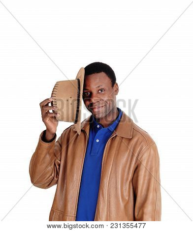 A Good Looking African American Man Holding His Brown Cowboy Hat, Standing In A Leather Jacket, Isol