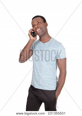 An Handsome African American Man Standing In A Gray T-shirt  Talking At His Cell Phone And Smiles, I