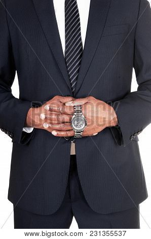 The Middle Section Of An African Man In A Dark Suit Holding His Wrist Watch In His Hands, Isolated F