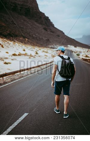 Traveler With Backpack Walks In The Center Of An Epic Winding Road. Huge Volcanic Mountains In The D