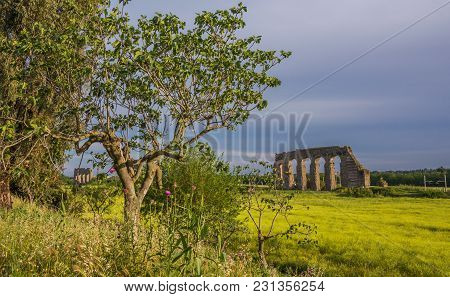 View Of Ancient Roman Aqueduct Ruins During Spring Season In Rome Countryside