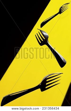 Three Forks Parallel On A Yellow Background.each Casting A Strong Shadow.art Of Shadow. Visual Art