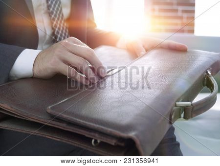 businessman's hand with suitecase in a modern office