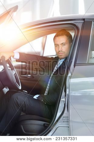 businessman sitting behind the wheel of a car, in the Parking lo
