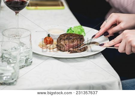 Woman Cuts A Piece Of Fresh Grilled Bbq Roast Beef Steak And Sauce On A White Plate With Green Leaf