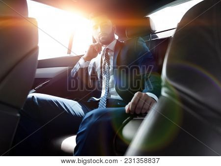 businessman talking on the phone while sitting in the back seat of his car