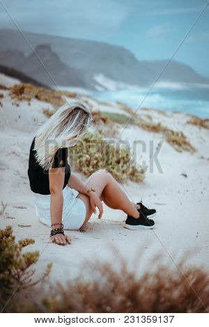 Woman Sitting On White Sand Dune With Barren Vegetation Admiring Coastline Landscape And Atlantic Oc