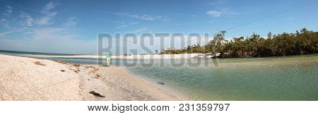 Older Woman Stands On The White Sand Beach In Front Of Aqua Blue Water Of Clam Pass