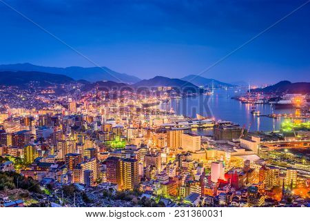Nagasaki, Japan downtown skyline over the bay from above at night.