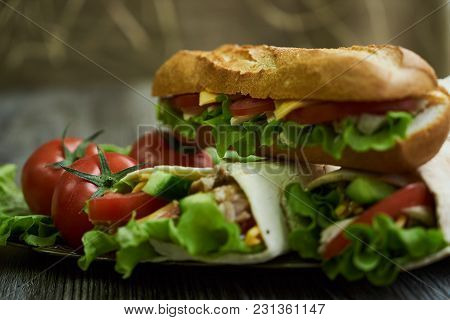 Shaurma Chicken Roll In A Pita With Fresh Vegetables And Long Subway Sandwich With Tomatoes, Cucumbe