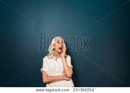 Photo of serious mature old woman isolated over dark blue background. Looking aside screaming talk to someone.