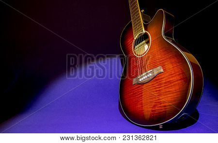 Portrait Of A Beautiful Electroacoustic Guitar Standing Sideways To The Right On A Blue And Black Ba