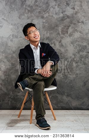 Full length portrait of a smiling young asian man dressed in suit sitting in a chair and looking away over gray background