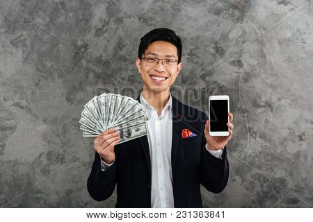 Portrait of a smiling young asian man dressed in suit holding bunch of money banknotes while showing blank screen mobile phone over gray background