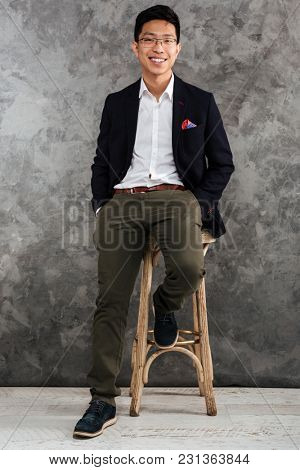 Full length portrait of a satisfied young asian man dressed in suit sitting in a chair over gray background