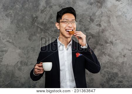 Portrait of a smiling young asian man dressed in suit drinking coffee and eating cookie over gray background