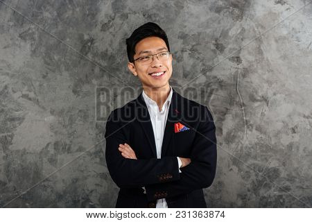 Portrait of a smiling asian man dressed in suit standing with arms folded and looking away over gray background