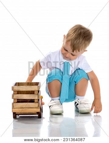 Cute Little Boy Is Playing With A Toy Wooden Car On A White Background In The Studio. The Concept Of
