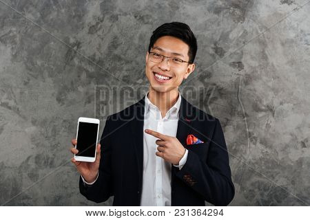 Portrait of a smiling young asian man dressed in suit pointing finger at blank screen mobile phone over gray background