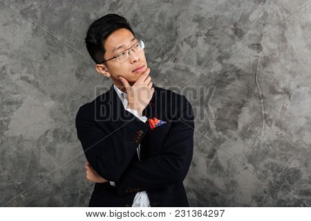 Portrait of a pensive young asian man dressed in suit thinking and looking away over gray background