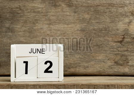 White Block Calendar Present Date 12 And Month June On Wood Background