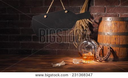 Glass Of Cognac With Barrel On Brick Backgroun