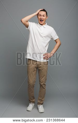 Photo of shocked young man standing isolated over grey wall background. Looking aside.