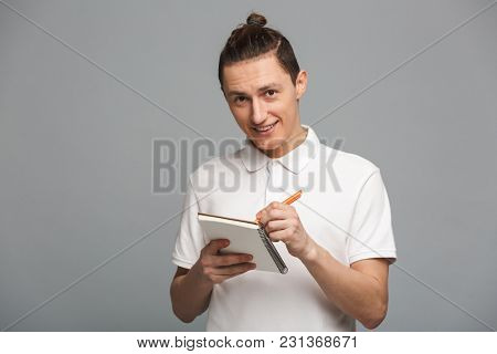 Image of cheerful young man standing isolated over grey wall background. Looking camera writing notes in notebook.