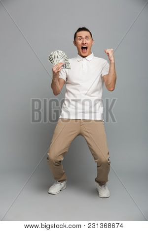 Photo of shocked screaming young man standing isolated over grey wall background. Looking camera holding money make winner gesture.
