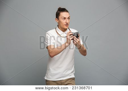 Photo of excited young man photographer standing isolated over grey wall background holding camera. Looking aside.