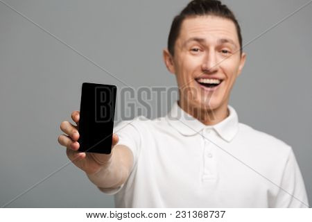 Photo of cheerful young man standing isolated over grey wall background. Looking camera showing display of mobile phone.