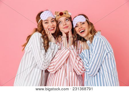 Three joyful girlfriends 20s wearing leisure clothings and sleep masks hugging and having fun at slumber party isolated over pink background