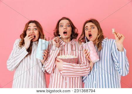 Three young girls 20s wearing colorful striped pyjamas expressing excitement or thrill while watching movie at slumber party and eating pop corn isolated over pink background