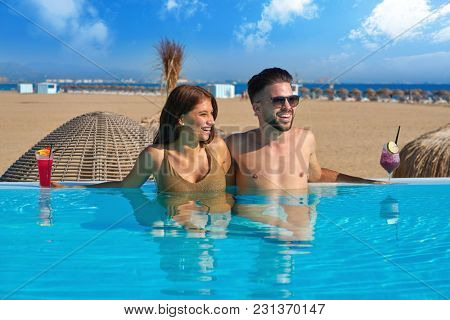 Tourist couple having bath in infinity pool on a beach resort with cocktails