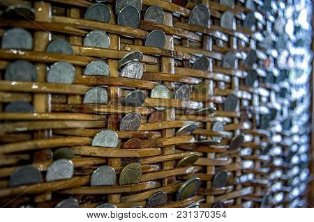 Coins In A Basket. Money In A Basket. Coins Of Various Types And Values Inserted In Between The Wove
