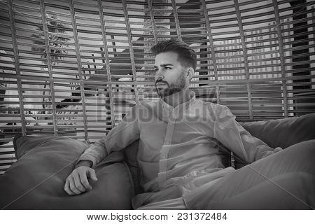 young beard man relaxed in a beach parasol hammock at summer