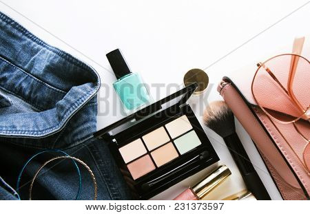 Top view of woman jeans shirt, concealer pallet, lip gloss, nail polish, bracelet, powder brush on white background