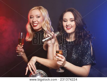 lifestyle and people concept: two beautiful young women with wine glasses and disco ball