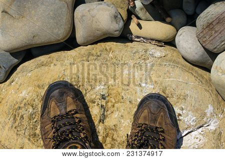 Hiking Boots, Boulders And Colorful Pebbles On The Beach On A Warm Summer Day